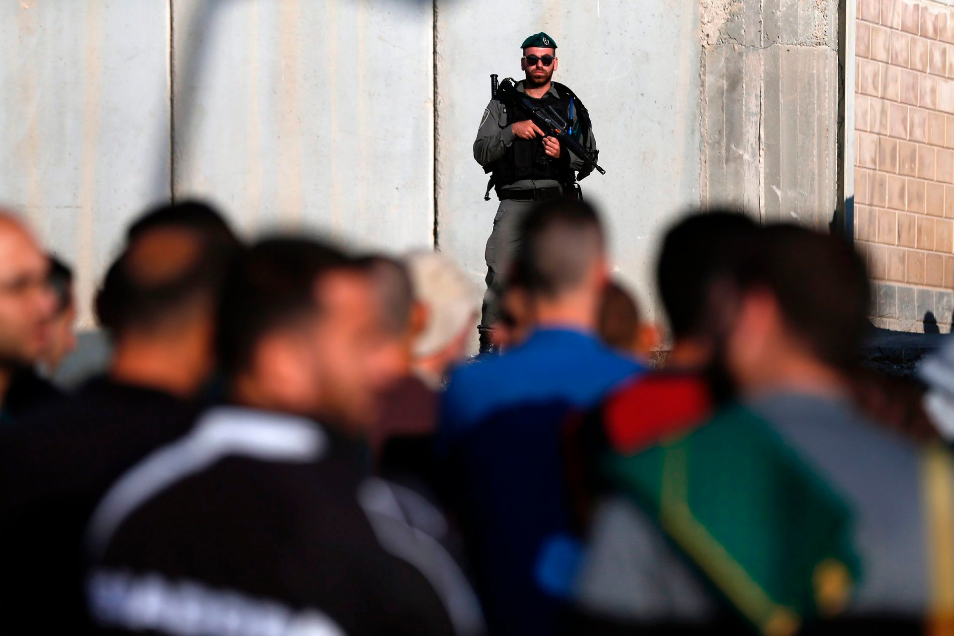 Israeli security forces stand guard as Palestinians wait to cross the Qalandiyah checkpoint between the West Bank city of Ramallah and Jerusalem, June 2, 2017.