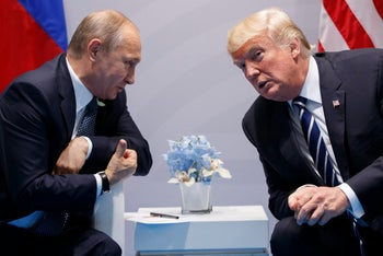 Vladimir Putin, left, talking with Donald Trump: The men are both seated, leaning attentively towards one another; they seem to be wearing identical dark blue suits but while Trump is wearing a striped tie, Putin's is checked. There is a small vase of what looks like fake light-blue flowers between them on a small white table. Trump has a tiny US flag pin in his lapel.