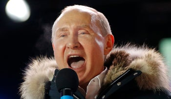 Russian President Vladimir Putin speaks to supporters during a rally near the Kremlin in Moscow. March 18, 2018. He is wearing a coat with a fur collar and seems to be almost yelling into a microphone.