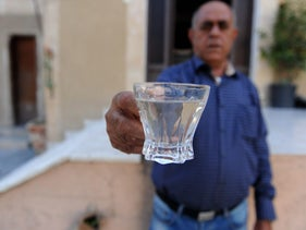 A resident of the northern Israeli town of Sha'ab holding a glass of murky tap water.
