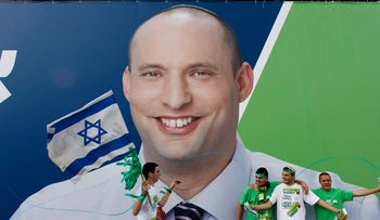 Supporters of the Habayit Hayehudi party stand in front of a campaign poster depicting the head of the party Naftali Bennett in Tel Aviv. January 16, 2013