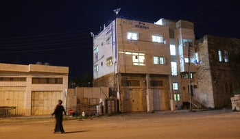 A resident of Hebron walks past the contested Beit Hamachpela building, March 22, 2018.