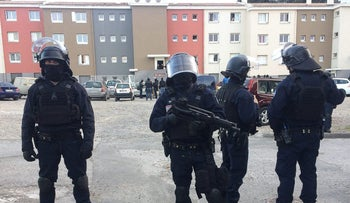 French members of the Research and Intervention Brigade (BRI) secure the area during a search operation at the Ozanam housing estate in Carcassonne, southwestern France on March 23, 2018.