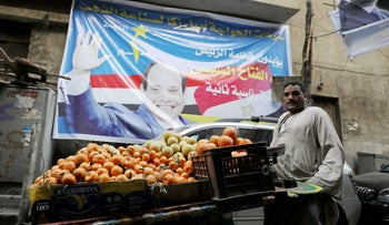 """A fruit seller is seen at a Cairo market near a campaign poster of Egypt's President Abdel Fattah al-Sissi that reads: """"All of us with you"""", March 19, 2018."""