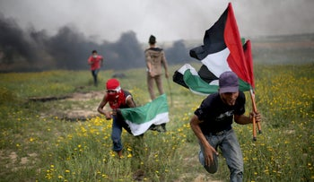 Palestinian demonstrators run during clashes with Israeli troops near the border with Israel, in the southern Gaza Strip, March 23, 2018.