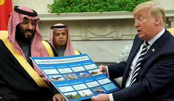 U.S. President Donald Trump holds a chart of military hardware sales as he welcomes Saudi Arabia's Crown Prince Mohammed bin Salman in the Oval Office at the White House in Washington, U.S. March 20, 2018