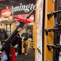 In this Jan. 15, 2013, file photo, accessories manufacturer Kevin Kao, of Irvine, Calif., examines a military grade Remington Adaptive Combat Rifle at the 35th annual SHOT Show in Las Vegas.
