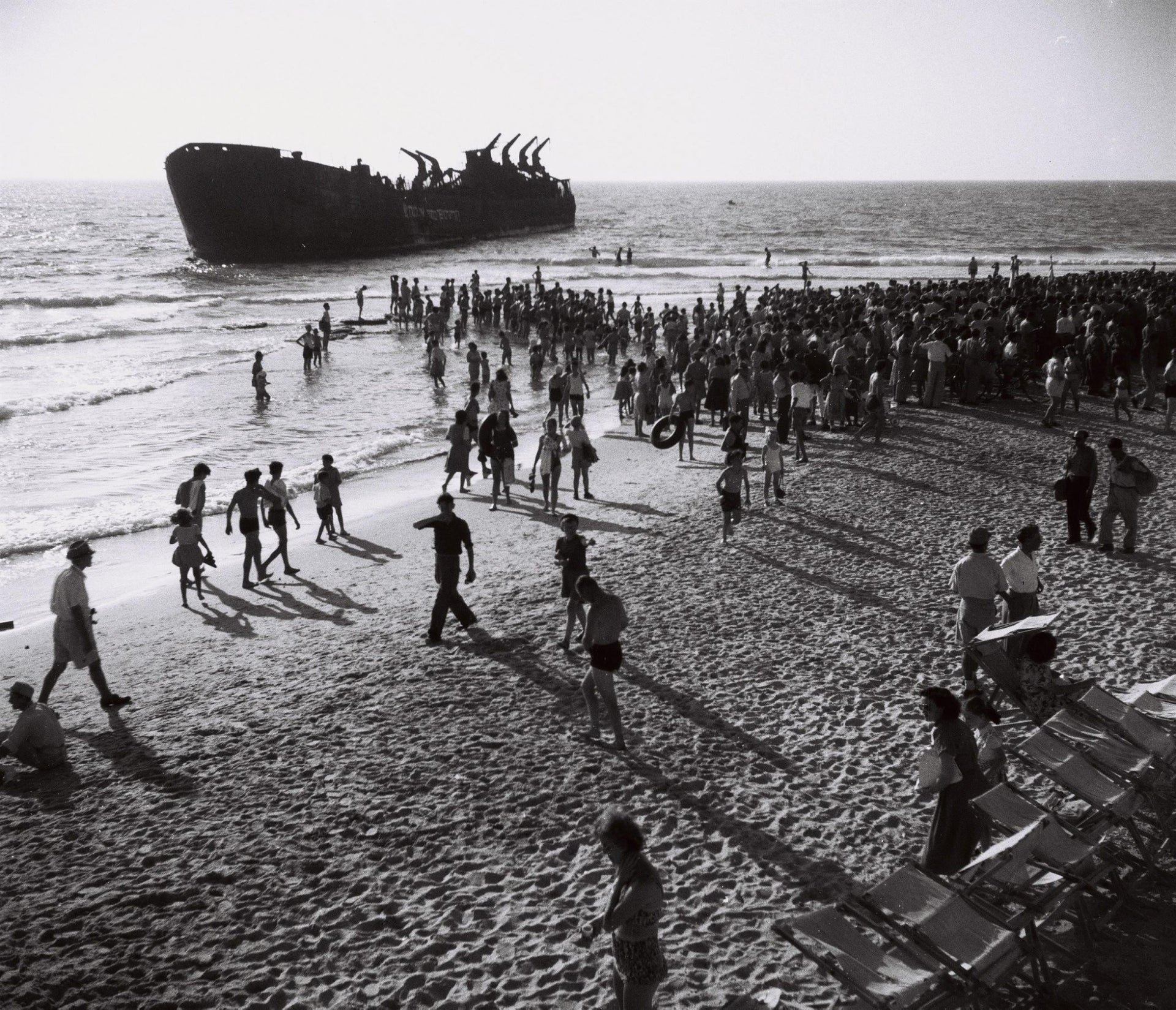 Members of the Herut movement gather at the Tel Aviv beach to watch the heruth memorial gathering on the 1st anniversary of the Atalena ship incident, June 1949.