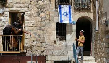 An Israeli flag hanging on a house as a settler looks at Palestinians in Hebron, in the occupied West Bank, March 27, 2018