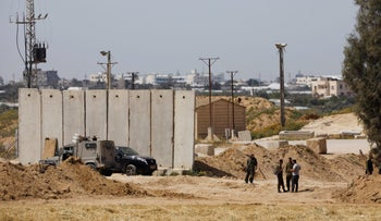Israeli soldiers stand next to a security barrier near the border between Israel and the Gaza Strip, March 18, 2018.