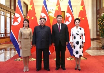 Chinese President Xi Jinping, second from right, and his wife Peng Liyuan, right, and North Korean leader Kim Jong Un, second from left, and his wife Ri Sol Ju, left, pose for a photo at the Great Hall of the People in Beijing.