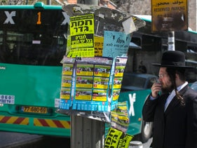 An ultra-Orthodox man standing on the street as a bus drives by.