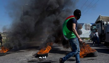 A masked Palestinian protester walks by burning tires during clashes with Israeli troops at the entrance to Ramallah on March 12, 2018.