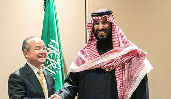 Masayoshi Son, chairman and chief executive officer of SoftBank Group Corp., left, shakes hands with Mohammed bin Salman, Saudi Arabia's crown prince, after signing an agreement in New York, U.S., on Tuesday, March 27, 2018