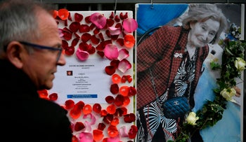 """A man stands in front of a picture of Mireille Knoll and a message announcing a """"Marche Blanche"""" condemning the alleged anti-Semitic motive for of her killing, placed on the fence surrounding her building in Paris on March 27, 2018."""