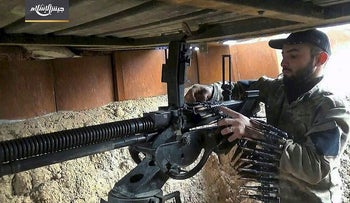 This photo posted Tuesday, Feb 20, 2018, by the Syrian insurgent group Army of Islam, shows a fighter with the Army of Islam, as he loads a heavy machine gun with bullets, in the suburbs of the Syrian capital Damascus