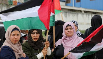 Women wave their national flags during a rally marking the 41st anniversary of Land Day, on the Palestinian side of the Beit Hanoun border crossing between Israel and the Gaza Strip, Thursday, March 30, 2017.