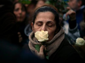 A woman holds a white rose as she stands outside Mireille Knoll's apartment during a silent march in Paris, France, Wednesday, March 28, 2018. Family members, friends and France's president have honored an 85-year-old woman who escaped the Nazis 76 years ago but was stabbed to death last week in her Paris apartment, apparently targeted because she was Jewish. Mireille Knoll's death has taken on national importance, reminding France of both historic anti-Semitism and its resurgence in some quarters in recent years.  (AP Photo/Thibault Camus)