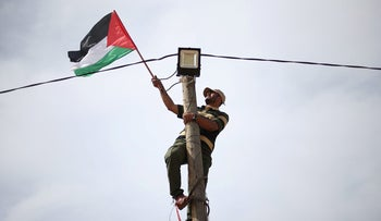 A man hangs a Palestinian flag at an electric pole near the border with Israel, in the southern Gaza Strip, March 28, 2018.