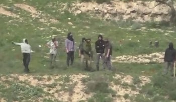 Jewish settlers, next to soldiers, attacking Palestinians near Einabus, in the Nablus area.