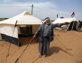 A Palestinian man gestures outside a tent near the Gaza order with Israel, March 28, 2018.