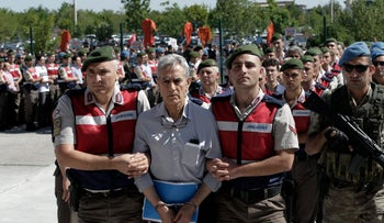 Akin Ozturk, former Air Force commander is escorted outside the courthouse as nearly 500 suspects accused of leading the failed coup attempt arrive for trial in Ankara, Aug. 1, 2017.