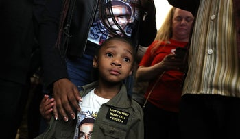 A young girl wears an image of Stephon Clark, an unarmed black man shot and killed by police officers in the backyard of his grandmother's house. Black Lives Matter demonstration, Sacramento, California. March 22, 2018