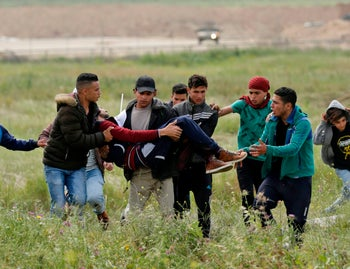 A picture taken on March 30, 2018 shows an injured Palestinian youth being carried by other protesters as they flee during clashes after a demonstration near the border with Israel east of Gaza City commemorating Land Day.