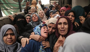 Relatives of a Palestinian man who was killed in Friday's clashes cry during his funeral in the northern of Gaza Strip on March 31, 2018.