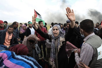 Palestinian protesters wave their national flag and gesture during a demonstration commemorating Land Day near the border with Israel, March 30, 2018.