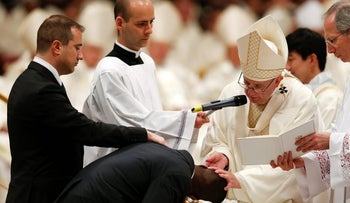 Pope Francis baptizes Nigerian John Ogah, 31, next to his godfather Italian carabinieri Nunzio Carbone (L), during the Easter Vigil at St Peter's basilica on March 31, 201 in Vatican.