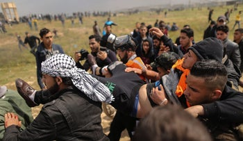 Photo taken on March 30, 2018 shows an injured Palestinian youth being carried by other protesters as they flee during clashes after a demonstration near the border with Israel, commemorating Land Day