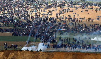 Israeli soldiers shoot tear gas from the Israeli side of the Israel-Gaza border, as Palestinians protest on the Gaza side of the border, March 30, 2018.