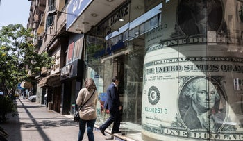 A pedestrian enters a currency exchange bureau adorned with a U.S. one dollar bill in Cairo, Egypt on March 31, 2018.