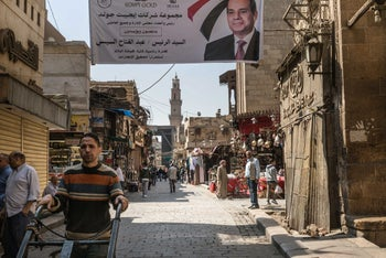A worker pushes a dollie under an election banner in support of Abdel-Fattah El-Sisi, Egypt's president, in Cairo, Egypt on March 31, 2018.