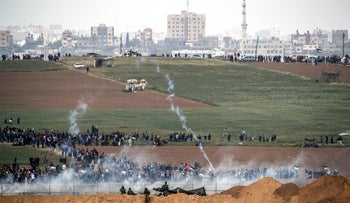 Israeli soldiers shoot tear gas toward Palestinians protesters as they gather on the Israel-Gaza border on Friday, March 30 2018.