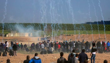 Israeli troops fire teargas canisters at Palestinians during a demonstration near the Gaza Strip border, March 30, 2018.