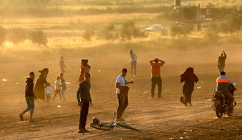 Palestinian protesters run for cover from tear gas fired by Israeli security forces east of Gaza City in the Gaza strip on March 31, 2018