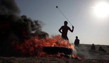 A Palestinian protester hurls stones toward Israeli soldiers during a protest near the Gaza border with Israel, March 31, 2018.
