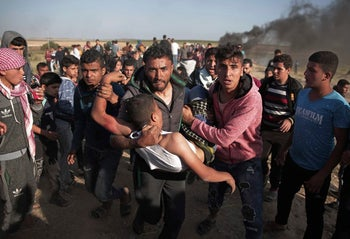 Palestinian protesters carry a wounded man shot by Israeli troops during a protest near the Gaza Strip border with Israel, March 31, 2018.