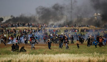 Teargas canisters fired by Israeli troops fall during a demonstration near the Gaza Strip border with Israel, March 30, 2018.
