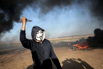A Palestinian wearing an Anonymous mask holds a knife during clashes with Israeli security forces near the border at Khan Yunis, Gaza, April 1, 2018.