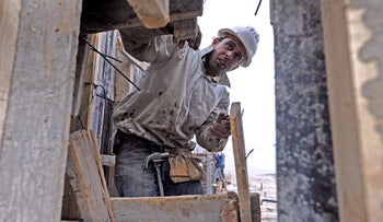 A Palestinian worker checks fixings on a new housing development at Ma'aleh Adumim, an Israeli settlement in the West Bank