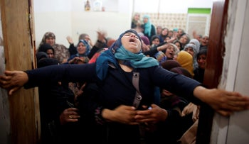 Mourners hold back a relative of Palestinian Hamdan Abu Amshah, who was killed along Israel's border with Gaza, during his funeral in Beit Hanoun town, in the northern Gaza Strip March 31, 2018.