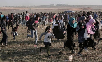 Palestinian protesters run for cover from teargas fired by Israeli soldiers during clashes with troops along the Israel-Gaza border, March 31, 2018.