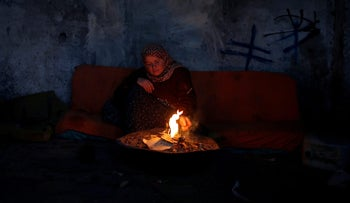 A Palestinian woman warms herself by a fire inside her house on a winter day, Gaza Strip, January 31, 2018.