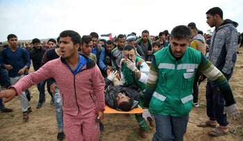 FILE PHOTO: Palestinians in the Gaza Strip evacuate a wounded man from the demonstrations near the border with Israel, March 30, 2018.
