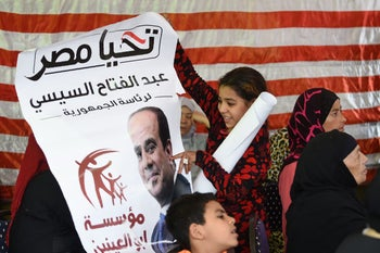 A girl looks at a poster for President Abdel-Fattah al-Sissi on the third day of the presidential election, Giza, March 28, 2018.
