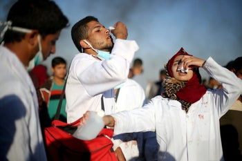 Female Palestinian medic Razan Al-Najar reacts to tear gas as she works at the scene of clashes at Israel-Gaza border, in the southern Gaza Strip, April 1, 2018.