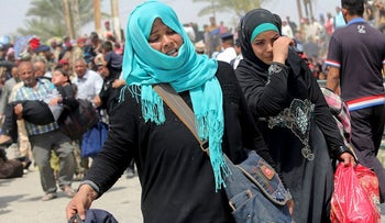 Displaced Sunni women fleeing the violence in Ramadi, carry bags as they walk on the outskirts of Baghdad, May 24, 2015